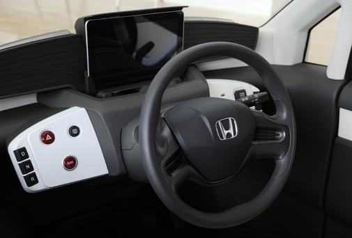 The Honda Motor Co. logo is displayed on the steering wheel of a Micro Commuter prototype electric vehicle.