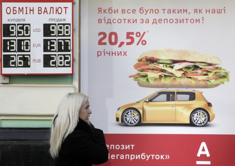 A woman speaks on the phone near a board with currency exchange rates in Kiev, February 26, 2014. Photo: Reuters/Konstantin Chernichkin