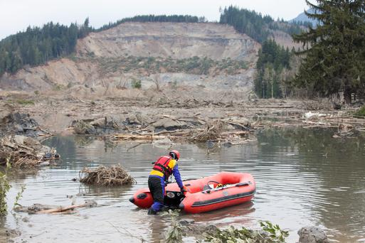 A search and rescue worker begins looking for survivors in the aftermath of the mudslide