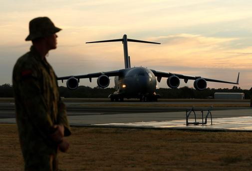 An Australian Air Force serviceman watches as an Australian Air Force C-17 taxis on the tarmac of the RAAF Base Pearce near Perth. The C-17 delivered an Australian Navy SeaHawk helicopter to the base which will be used in the search for Malaysian Airlines flight MH370 in the southern Indian Ocean.