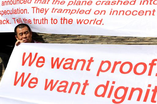 A family member of a passenger onboard the Malaysia Airlines Flight MH370 holds a banner during a protest outside Lido Hotel in Beijing March 29, 2014. The protest was also held to thank overseas Chinese who protested in front of the Malaysian Embassy in London on Thursday. Fresh objects spotted by planes searching for a missing Malaysian passenger jet in a new area of the southern Indian Ocean have again raised hopes of unravelling the three-week old mystery. REUTERS/Jason Lee (CHINA - Tags: TRANSPORT DISASTER CIVIL UNREST)