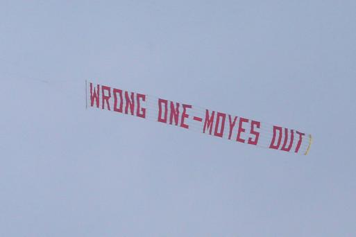A plane flies overhead with a banner criticising Manchester United Manager David Moyes during the Barclays Premier League match between Manchester United and Aston Villa at Old Trafford
