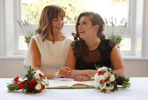 Couple Sarah Keith (L) and Emma Powell pose with the register during their same-sex wedding at the Claremont Hotel in Brighton
