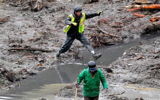 A rescue worker jumps over water in the search for victims of the mudslide in Oso, Washington