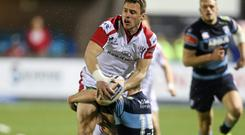 Ulster and Ireland winger Tommy Bowe tries to offload the ball after being tackled by Dan Fish of Cardiff Blues during the Celtic League clash at Cardiff Arms Park, Cardiff