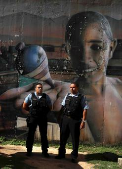 Police officers from the Pacifying Police Unit (UPP) stand guard in front of graffiti at the Complexo do Alemao slum in Rio de Janeiro. Photo: Reuters/Pilar Olivares