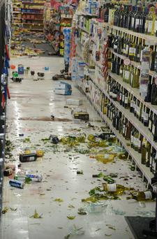 Broken bottles are seen on the floor in an aisle of a CVS pharmacy after a magnitude 5.1 earthquake in Fullerton, California March 29, 2014. Photo: Reuters/Gene Blevins