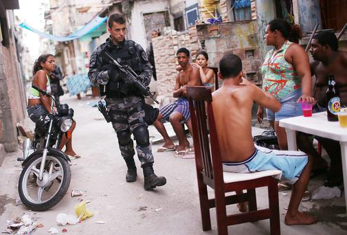 A Brazilian military police officer patrols after entering the unpacified Complexo da Mare, one of the largest 'favela' complexes in Rio