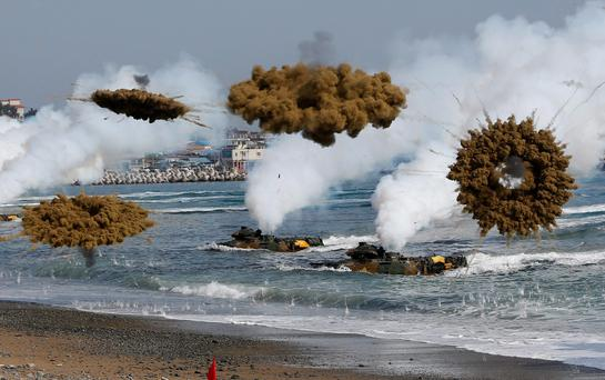Amphibious assault vehicles of the South Korean Marine Corps throw smoke bombs as they move to land on shore during a U.S.-South Korea joint landing operation drill in Pohang March 31, 2014.