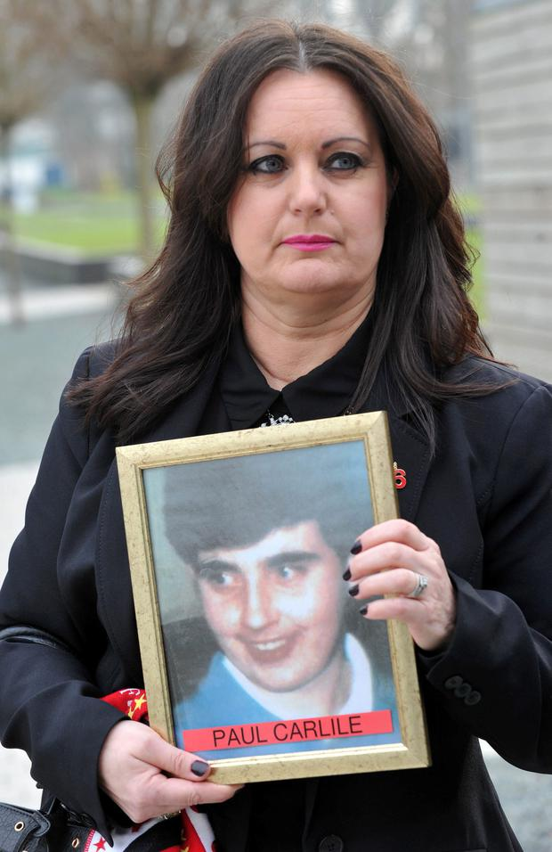 Donna Miller, with a photo of her brother Paul Carlile, arrives at Birchwood Park, Warrington, Cheshire for the opening of the inquest into the Hillsborough disaster.