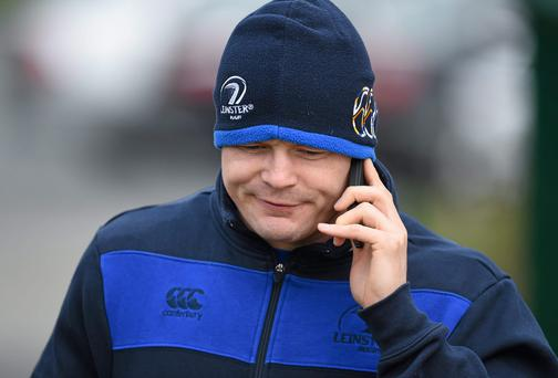 Brian O'Driscoll takes a call on the way to Leinster's training session at UCD yesterday