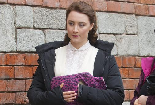 "Saoirse Ronan keeps warm with a hot-water bottle on the set of ""Brooklyn"" at Enniscorthy. Picture: Patrick Browne"