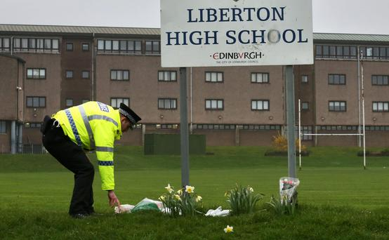 A policeman lays flowers from a member of the public outside Liberton High School in Edinburgh where a pupil died after a wall inside the school collapsed onto her. Photo: David Cheskin/PA Wire