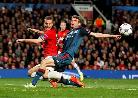 Manchester United's Nemanja Vidic challenges Bayern Munich's Thomas Mueller (R) during their Champions League quarter-final first leg soccer match at Old Trafford in Manchester, April 1, 2014. REUTERS/Stefan Wermuth (BRITAIN - Tags: SPORT SOCCER)