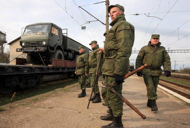 Russian servicemen stand in front of a military truck on a freight carriage at the settlement of Gvardeiskoye near the Crimean city of Simferopol