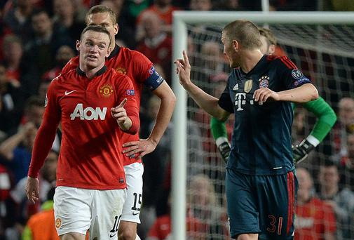 Bayern Munich's Bastian Schweinsteiger argues with Wayne Rooney after receiving a red card against Manchester United