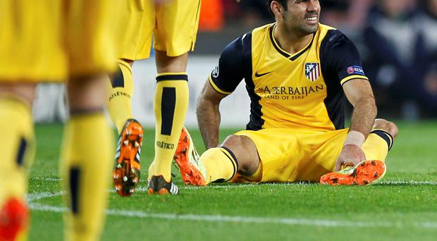 Atletico Madrid's Diego Costa sits in the pitch after injuring in his right leg during their Champions League quarter-final first leg soccer match against Barcelona at Camp Nou last night