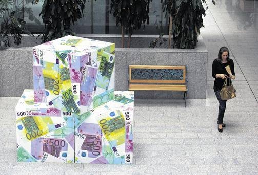 A woman walks past a sculpture based on euro bank notes in Nicosia, Cyprus.