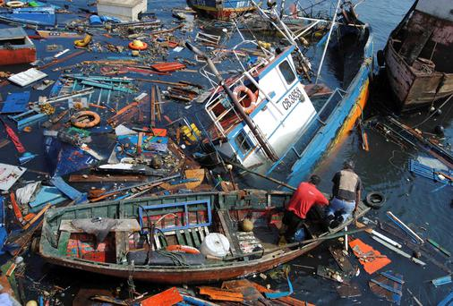 Fishermen try to salvage their boats in the aftermath of an earthquake and tsunami that hit the northern port of Iquique in Chile, April 2. The earthquake, with a magnitude of 8.2, struck off the coast of northern Chile near the copper exporting port of Iquique on Tuesday evening.
