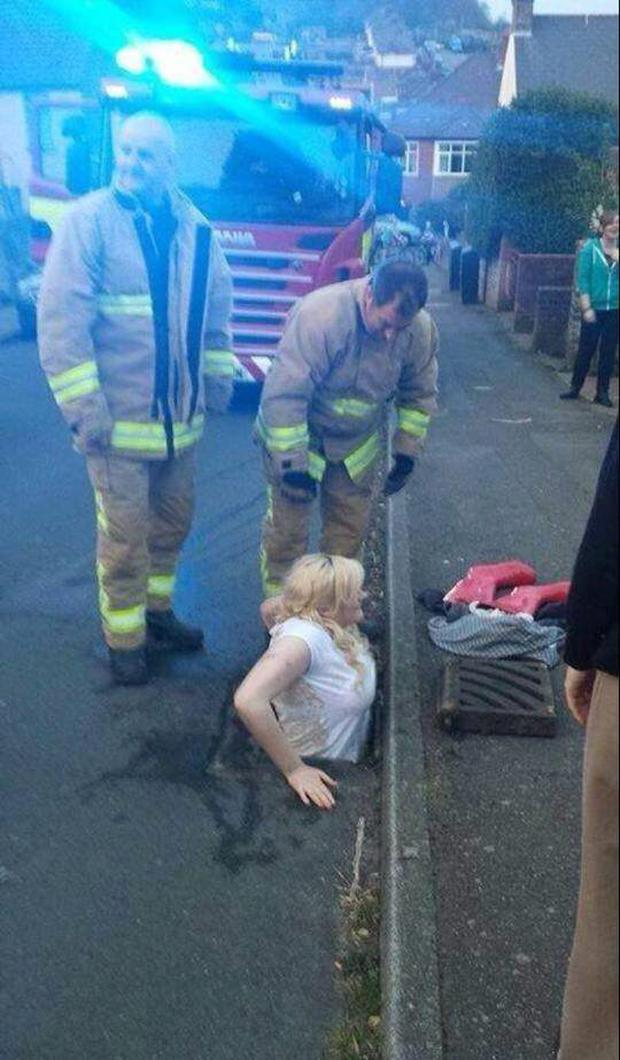 Ella Birchenough being rescued by firefighters after getting stuck in a storm drain while trying to retrieve her mobile phone. Photo: Tim Richards/PA Wire