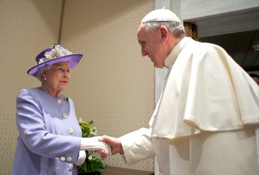 Queen Elizabeth (L) shakes hands with Pope Francis during a meeting at the Vatican. Reuters