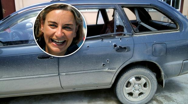 Bullet holes are seen in the car in which Associated Press photographer Anja Niedringhaus (inset) and AP reporter Kathy Gannon were traveling when they were shot by an Afghan policeman. AP / Reuters