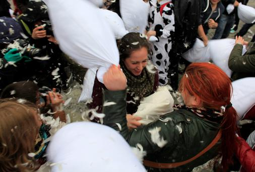 People take part in the International Pillow Fight Day in central Bucharest April 5, 2014. REUTERS/Radu Sigheti (ROMANIA - Tags: SOCIETY)