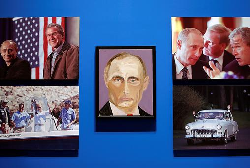 "A portrait of Vladimir Putin, President of Russia, painted by former US president George W. Bush is displayed between photographs as part of the exhibit, ""The Art of Leadership: A President's Personal Diplomacy"" at the George W. Bush Presidential Library and Museum in Dallas, Texas."