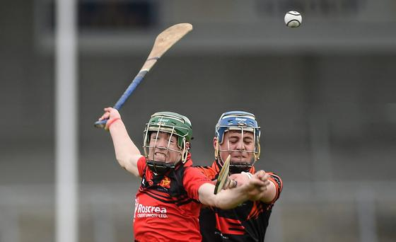 Jordan Fogarty, Coláiste Phobal, in action against Cormac McAllister, Cross & Passion