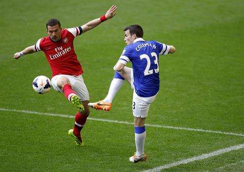 Everton's Seamus Coleman and Arsenal's Lukas Podolski battle for the ball
