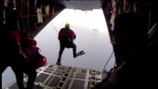 A member of the California Air National Guard's 129th Rescue Wing jumps off a military transport plane and into the ocean during a US military rescue mission
