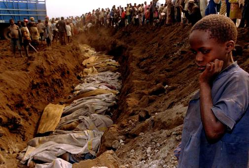 A Rwandan refugee girl stares at a mass grave where dozens of bodies have been laid to rest in this July 20, 1994 file photo. April 7, 2014 marks the 20th anniversary of the Rwanda genocide which killed 800,000 people.