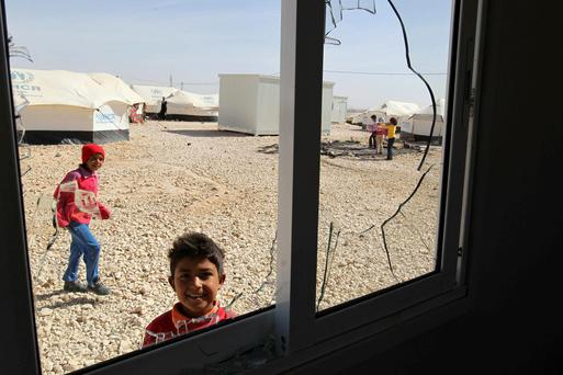 A Syrian refugee child is framed through a broken window as others (back) stand near the remains of their burnt belongings, a result of an outbreak of clashes between security forces and Syrian refugees at the Al-Zaatri refugee camp in the Jordanian city of Mafraq, near the border with Syria, April 6, 2014.