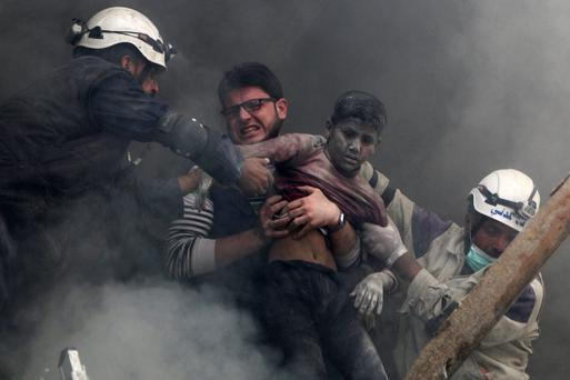 Men rescue a boy from under the rubble after an attack in Syria