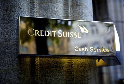 An illuminated logo sits on a wall outside a Credit Suisse Group AG office in Zurich, Switzerland