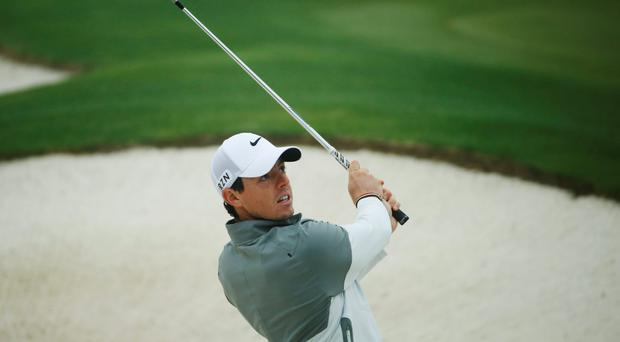 Rory McIlroy, of Northern Ireland, watches his bunker shot while on the practice range in preparation for the Masters golf tournament
