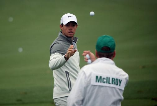 Rory McIlroy catches a ball from caddie JP Fitzgerald during a practice round prior to the start of the 2014 Masters Tournament at Augusta National Golf Club