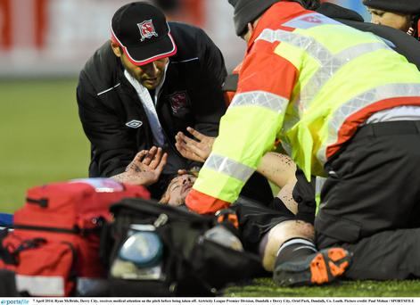 Ryan McBride, Derry City, receives medical attention on the pitch before being taken off.