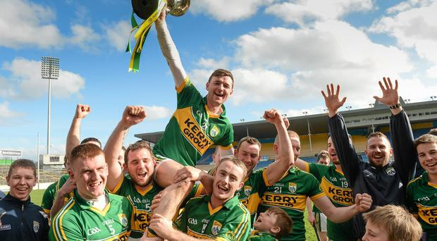 Kerry captain John Egan lifts the cup as his team-mates celebrate