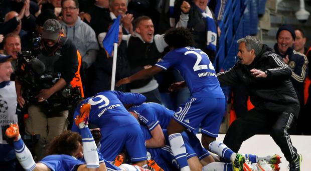 Chelsea's Demba Ba (hidden) celebrates with coach Jose Mourinho ( and team mates after scoring the crucial second goal against Paris St Germain at Stamford Bridge.