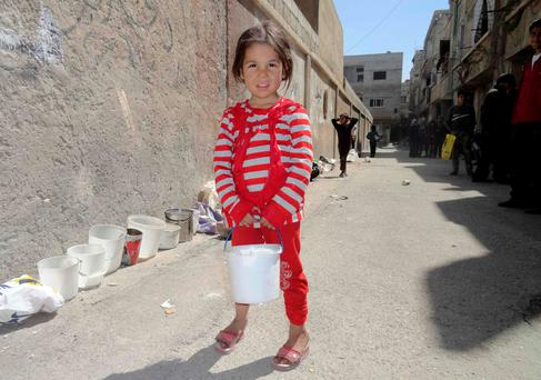 A girl poses for a photograph as she waits for food to be distributed in the besieged al-Yarmouk camp, south of Damascus REUTERS/Rame Alsayed