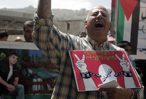 A Palestinian protester holds up a placard with an Arabic slogan that rejects linking the issue of the prisoners to the extension of the peace talks with Israel