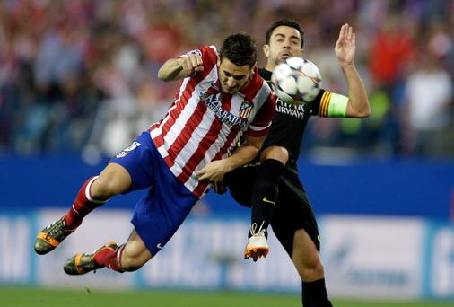 Atletico's Koke, left, fights for the ball with Barcelona's Xavi Hernandez during the Champions League quarterfinal second leg soccer match between Atletico Madrid and FC Barcelona in the Vicente Calderon stadium in Madrid, Spain, Wednesday, April 9, 2014. (AP Photo/Paul White)