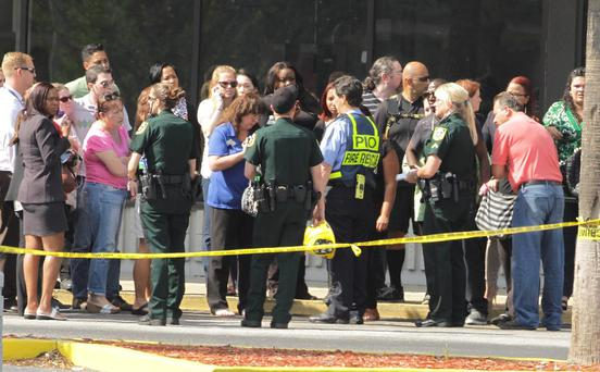 Parents and onlookers speak to police officers after a vehicle crashed into a child care center in Winter Park, Florida April 9, 2014. REUTERS/Stephen M. Dowell/Orlando Sentinel