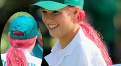 ACaroline Wozniacki looks on at the 2014 Par 3 Contest prior to the start of the 2014 Masters Tournament at Augusta sporting very bright pink hair