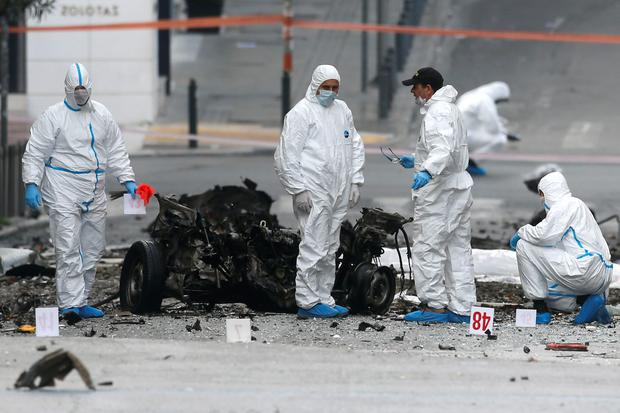 Forensic experts search for evidence on a street where a car bomb went off in Athens April 10, 2014. A car bomb went off outside a Bank of Greece building in central Athens early on Thursday, smashing windows in nearby shops but causing no injuries, police and Reuters witnesses said. The blast struck hours before Greece planned its first foray into the international bond markets since it plunged into a debt crisis four years ago, and a day before a visit by German Chancellor Angela Merkel. REUTERS/Alkis Konstantinidis