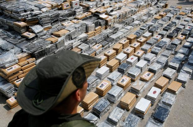An anti-narcotics policeman guards confiscated packs of cocaine in Cartagena