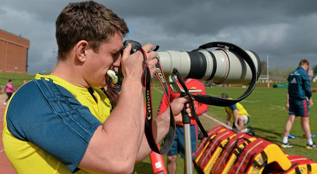Munster's Ian Keatley takes some pictures on a press photographer's camera during training at UL