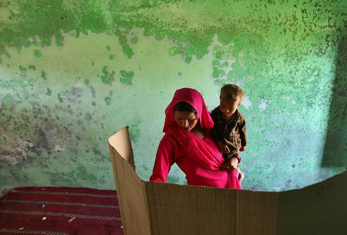 A woman holding her child votes for the general election inside a polling station on the outskirts of Jammu. Around 815 million people have registered to vote in the world's biggest election - a number exceeding the population of Europe and a world record - and results of the mammoth exercise, which concludes on May 12, are due on May 16