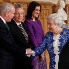 Queen Elizabeth II greets Northern Ireland's Deputy First Minister Martin McGuinness (left), First Minister Peter Robinson (2nd left) and Secretary of State for Northern Ireland Theresa Villiers (3rd left) as Irish President Michael D Higgins looks on (right) during a Northern Ireland-themed reception at Windsor Castle, during the first State visit to the UK by an Irish President. Luke MacGregor/PA Wire